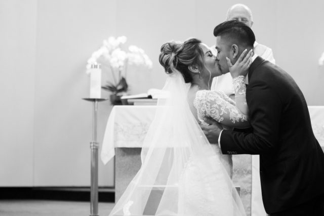 A bride and groom share their first kiss in front of a priest in Burnaby, BC.