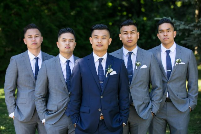 A groom stands with his 4 groomsmen in matching grey suits and looks into the camera near Deer Lake, BC.
