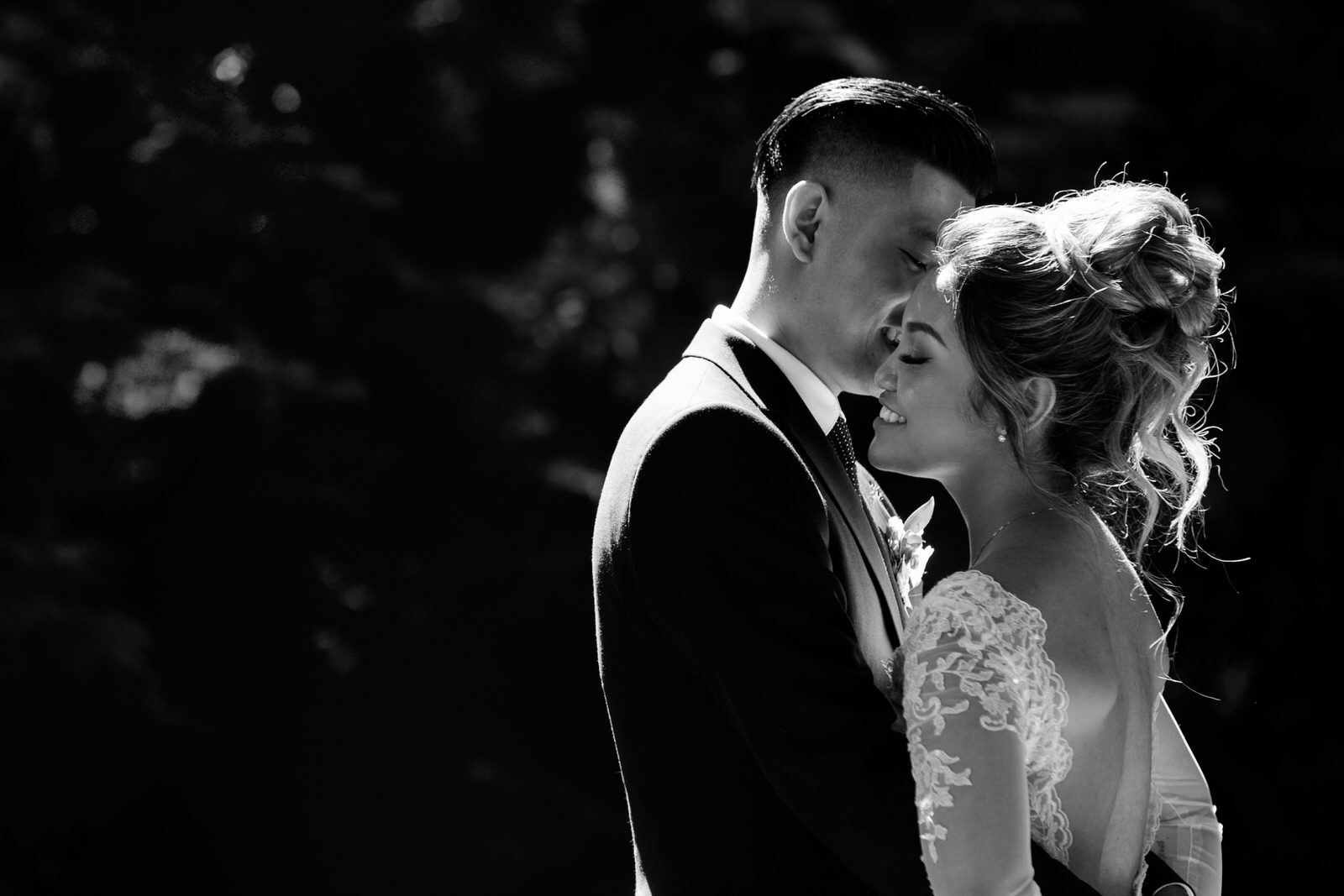A bride and groom embrace in a black and white photo taken near Deer Lake in Burnaby, BC.