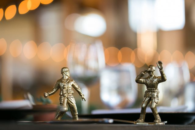 Two plastic army men painted gold sit on tables at Riverway Golf Course in Burnaby, BC. Photo by Clint Bargen Photography.