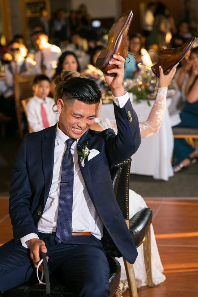 A groom laughs as he holds up his brown shoe at Riverway Golf Course in Burnaby, BC. Photo by Clint Bargen Photography.