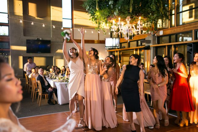 A group of girls jumps to catch a bouquet at Riverway Golf Course in Burnaby, BC. Photo by Clint Bargen Photography.