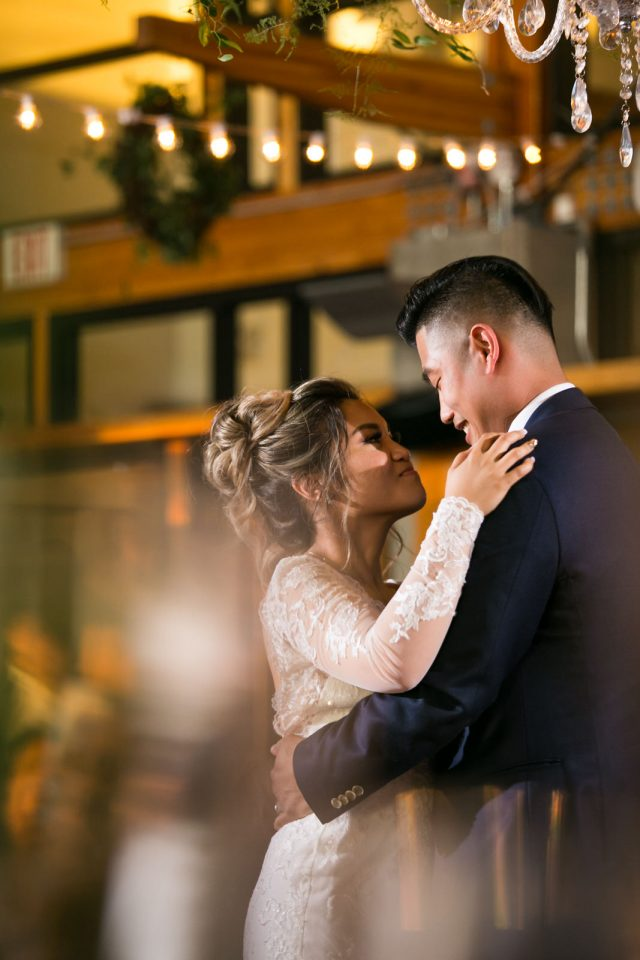 A bride and groom embrace on their wedding day at Riverway Golf Course in Burnaby, BC.
