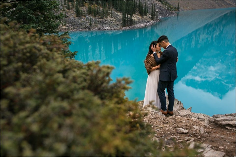 An asian couple embraces while she wears a brown fur shawl and he wears a blue suit at Lake Moraine near Banff, Alberta. Photo by Clint Bargen Photography.