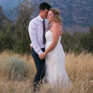 A newly married couple stands in tall grass near Olivier, BC at Covert Farms. Photo by Clint Bargen Photography.