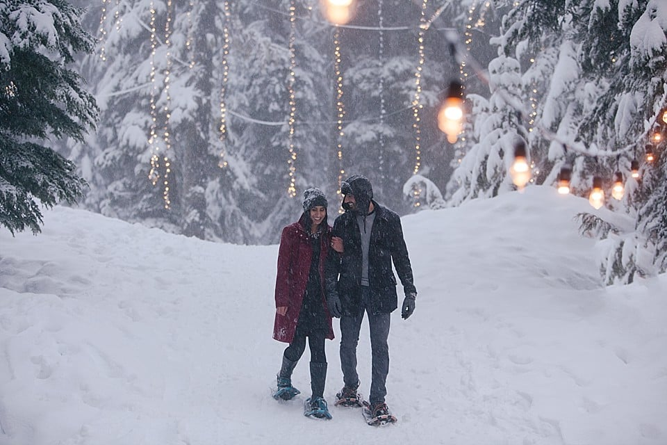 A young South Asian couple wear snowshoes and walk in the snow at Grouse Mountain in North Vancouver, BC.