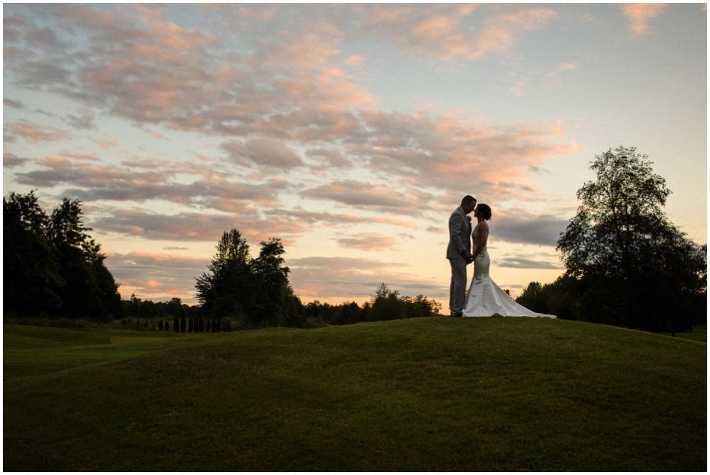 A bride in a white dress and a groom in a grey suit stand on a well groomed hill in front of a sunset at Golden Eagles Golf Course near Pitt Meadows, BC. Photo by Clint Bargen Photography.