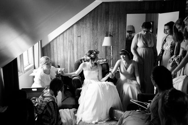 A bride holds hands and prays with her bridal party before her wedding.