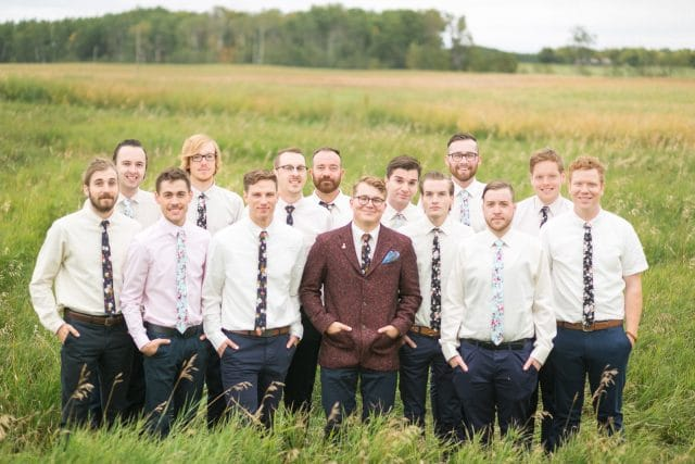A grooms stands in a tall grass field surrounded by 13 groomsmen by Clint Bargen Photography.