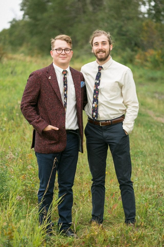 A groom poses with one of his groomsmen.