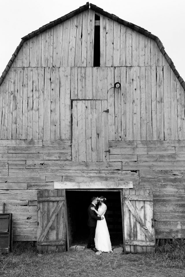 A wide shot of an entire rustic and vintage grey barn with a bride and groom putting their heads together.