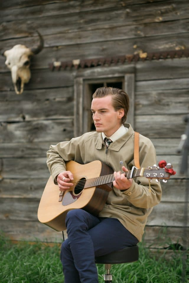 A young man plays guitar in front of an old rustic barn.
