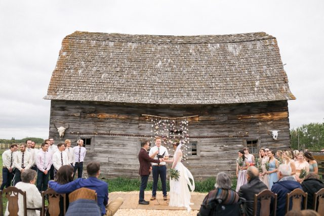 A groom in a red coat talks to his bride in front of an old rustic barn.