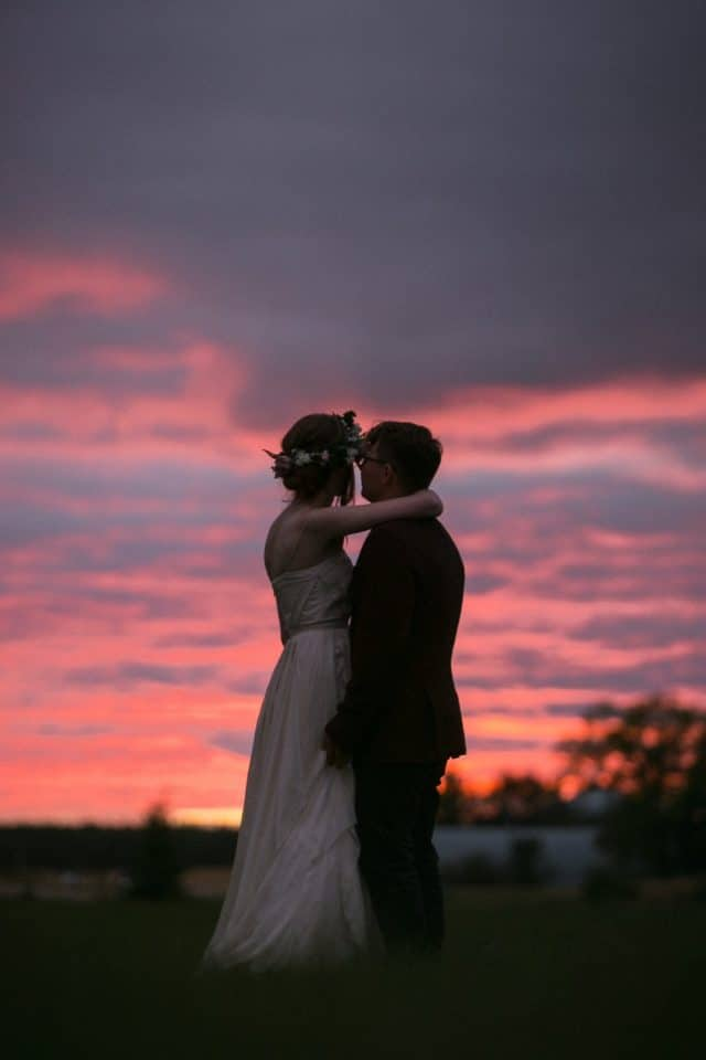 A bridal couple stand and watch the sunset in Saskatchewan by Clint Bargen Photography.