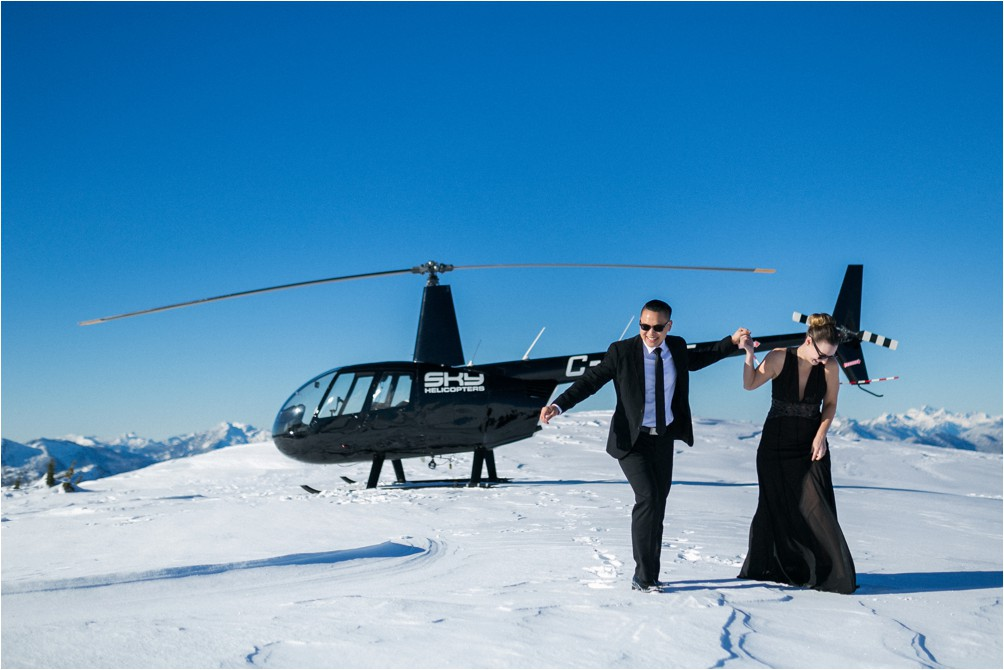 A married couple pose in front of a SKY Helicopter on top of the Thompson Mountain Range by Clint Bargen Photography.
