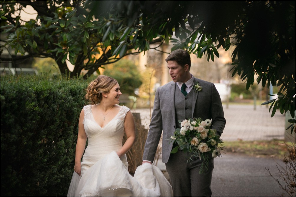 A bride and groom walk in some bushes by Clint Bargen Photography.