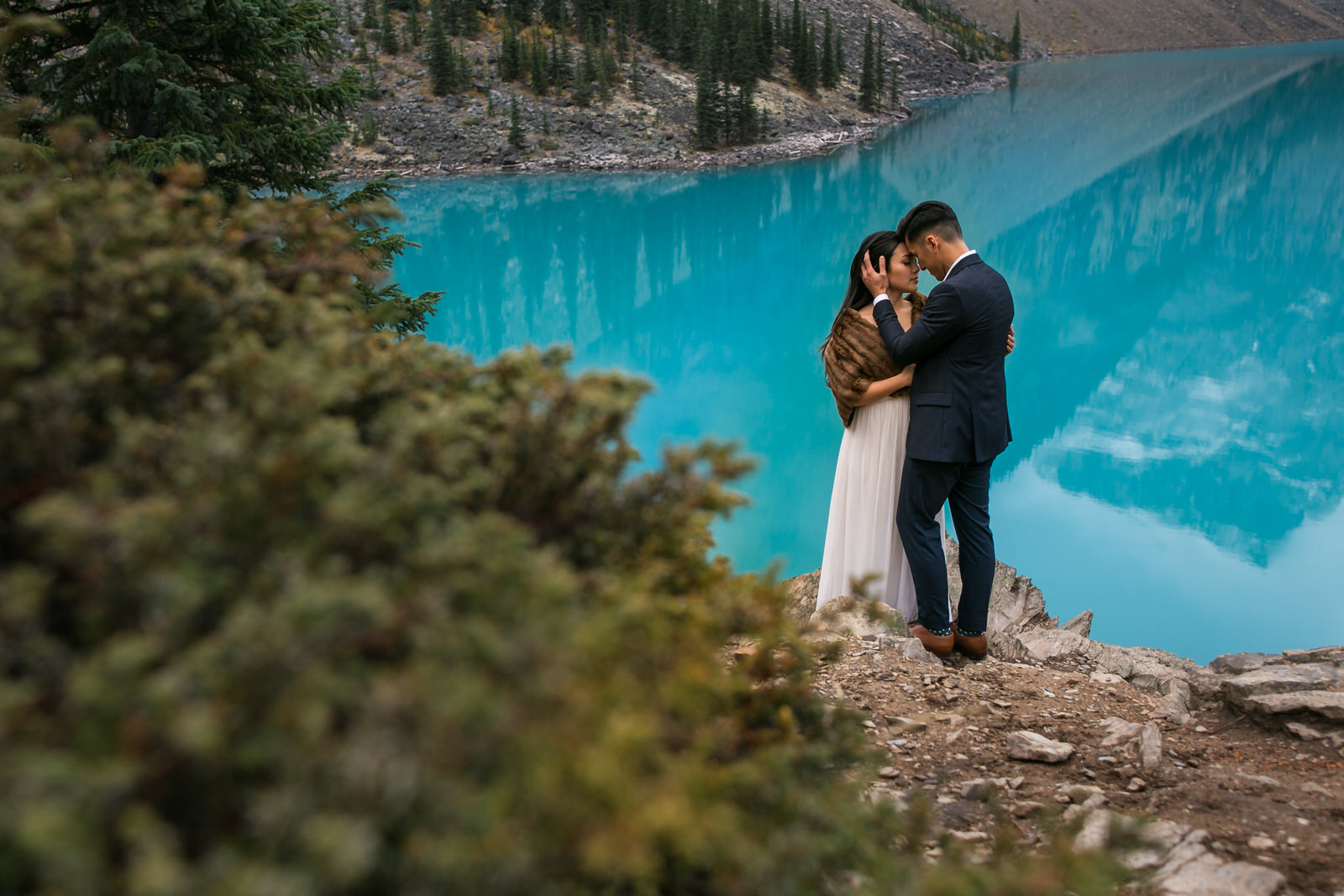 A well dressed Vietnamese couple embraces in front of a beautiful blue lake at Lake Moraine near Banff, Alberta. Photo by Clint Bargen Photography.