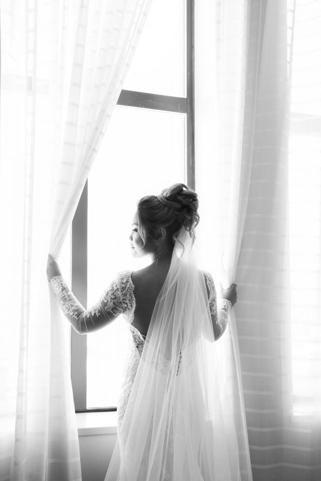 A bride opens the long curtains in her hotel room window at the Delta Marriot Hotel in Burnaby, BC.
