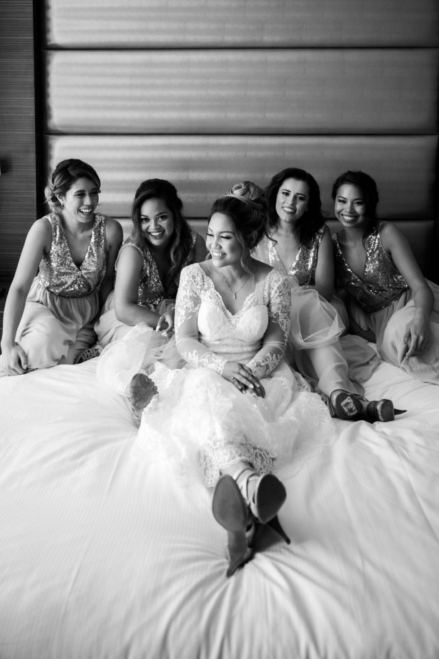 A bride sits on a bed surrounded by her four bridesmaids at Delta Hotel in Burnaby, BC.