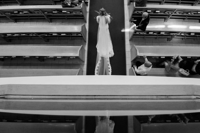 A bride walks down the aisle at St. Mary's Parish in Burnaby, BC. Photo by Clint Bargen Photography.