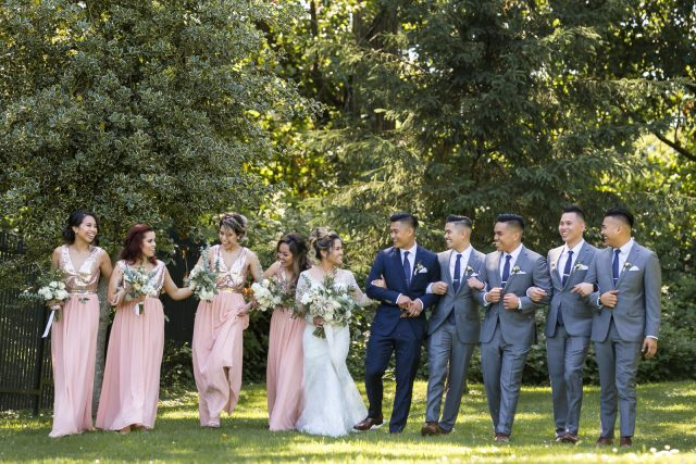 A bridal party of ten people walk together, arm in arm at Deer Lake Park in Burnaby, BC.