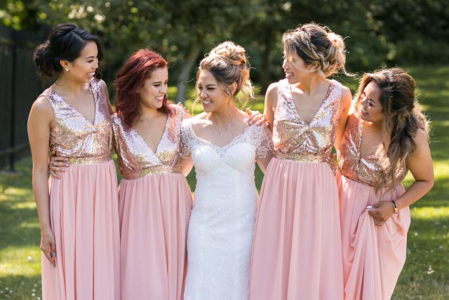 A bride surrounded by four bridesmaids in glittery pink dresses stand near Deer Lake in Burnaby, BC.