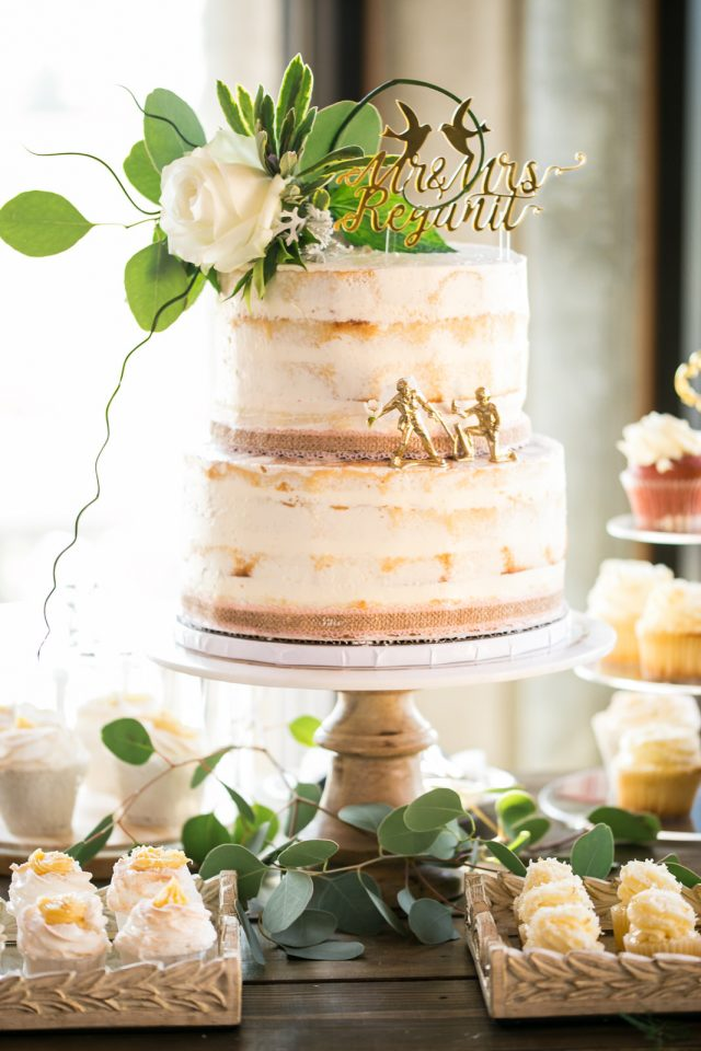 A wedding cake with gold decor that says
