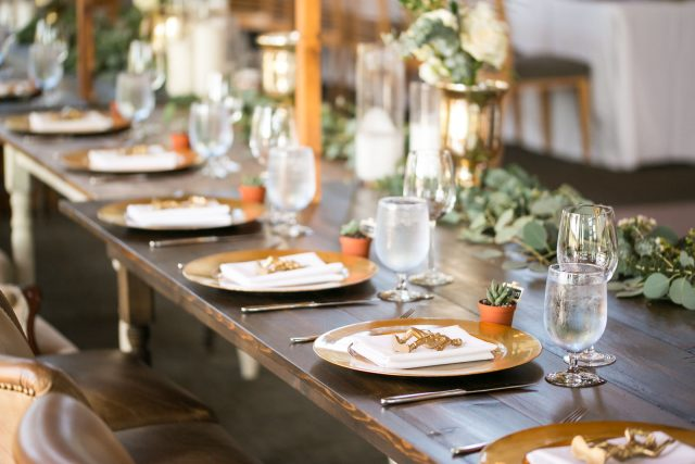 Close up wedding details of gold plates and a cactus plant at Riverway Golf Course in Burnaby, BC. Photo by Clint Bargen Photography.