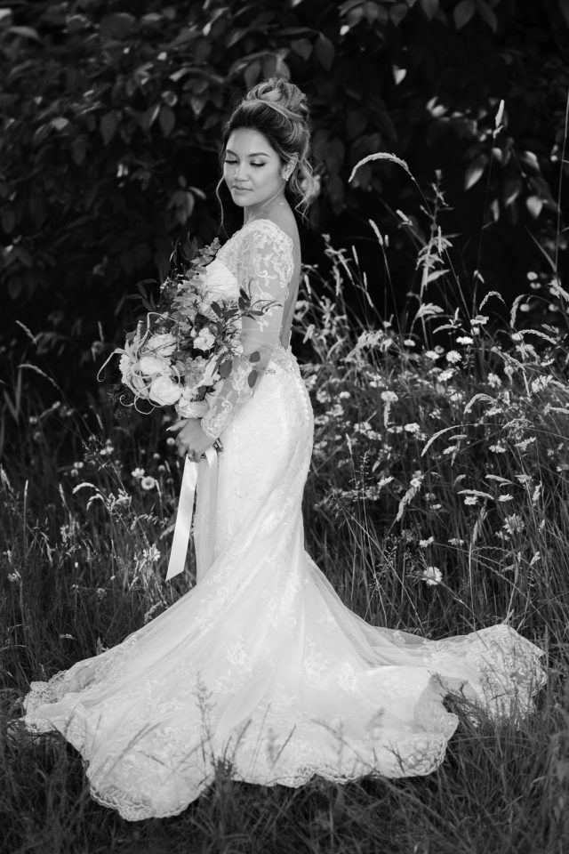 A bride looks back at her lace dress at Riverway Golf Course in Burnaby, BC. Photo by Clint Bargen Photography.