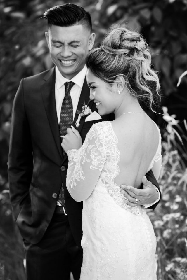 A bride and groom share a laugh in front of some bushes at Riverway Golf Course in Burnaby, BC. Photo by Clint Bargen Photography.