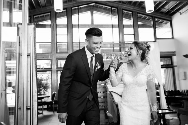 A bride and groom laugh as they enter the main ballroom at Riverway Golf Course in Burnaby, BC. Photo by Clint Bargen Photography.