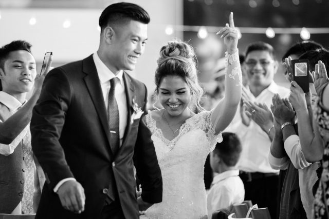 A black and white photo of a bride and groom entering their wedding reception as guests take photos of them on their cellphones at Riverway Golf Course in Burnaby, BC. Photo by Clint Bargen Photography.