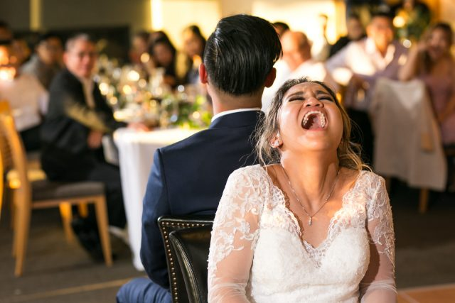 A bride laughs as she sits in a chair playing the shoe game at Riverway Golf Course in Burnaby, BC. Photo by Clint Bargen Photography.