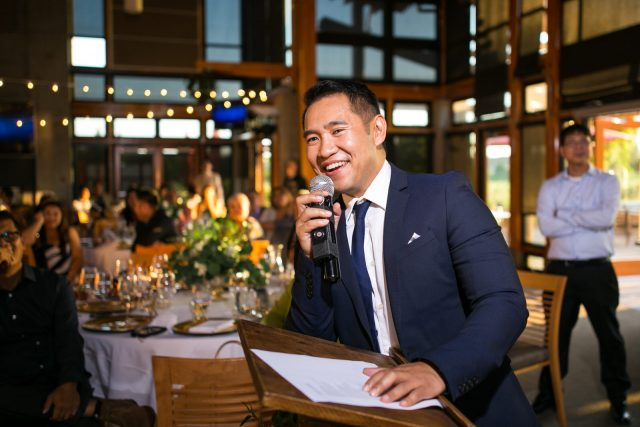 A wedding MC in a blue suit smiles as he narrates the shoe game at Riverway Golf Course in Burnaby, BC. Photo by Clint Bargen Photography.