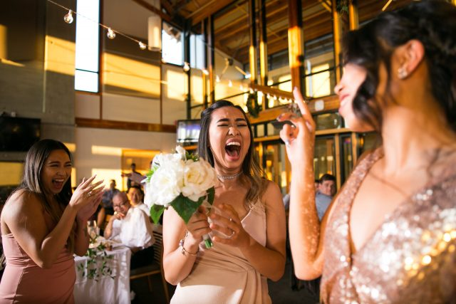 A young woman laughs after catching the bouquet at a wedding at Riverway Golf Course in Burnaby, BC. Photo by Clint Bargen Photography.