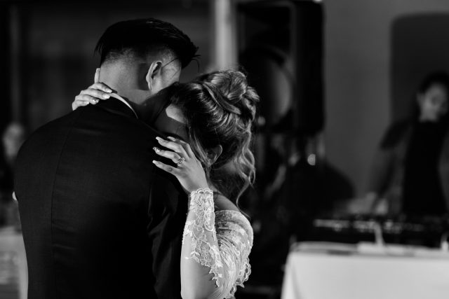 A black and white photo of a bride embracing her new husbands shoulder as she cries at Riverway Golf Course in Burnaby, BC.