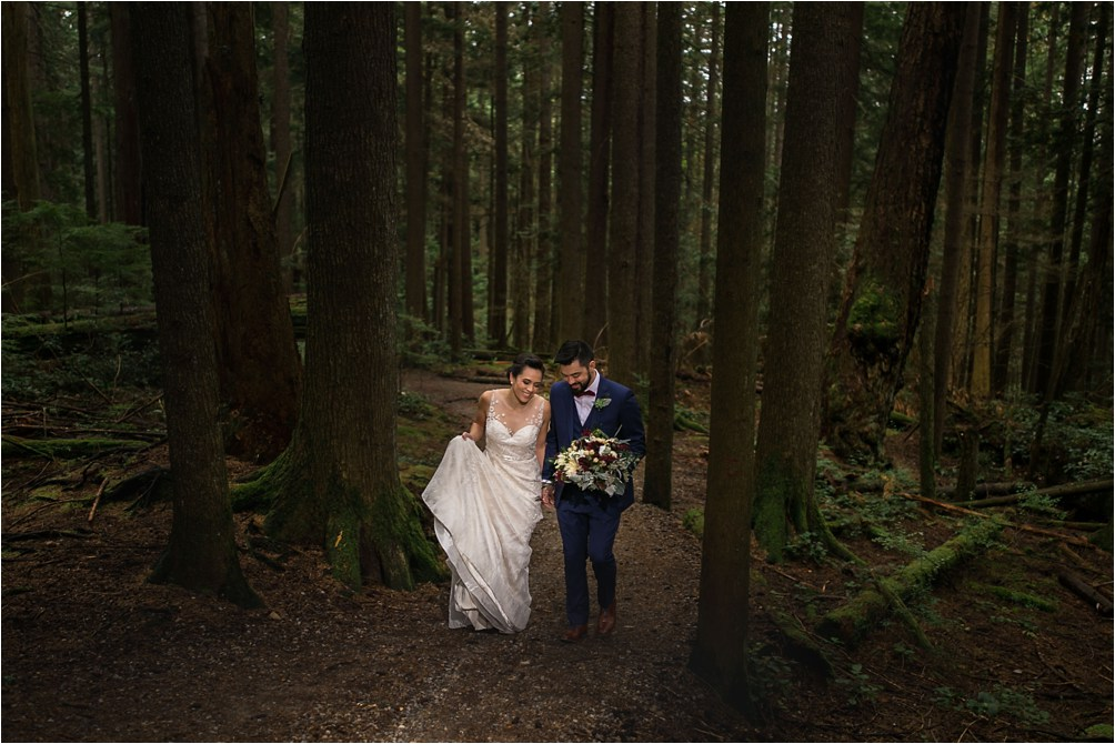 A bride and groom share a laugh as they walk in the Baden Powell Trail in a North Vancouver, BC forest. Image by Clint Bargen Photography.