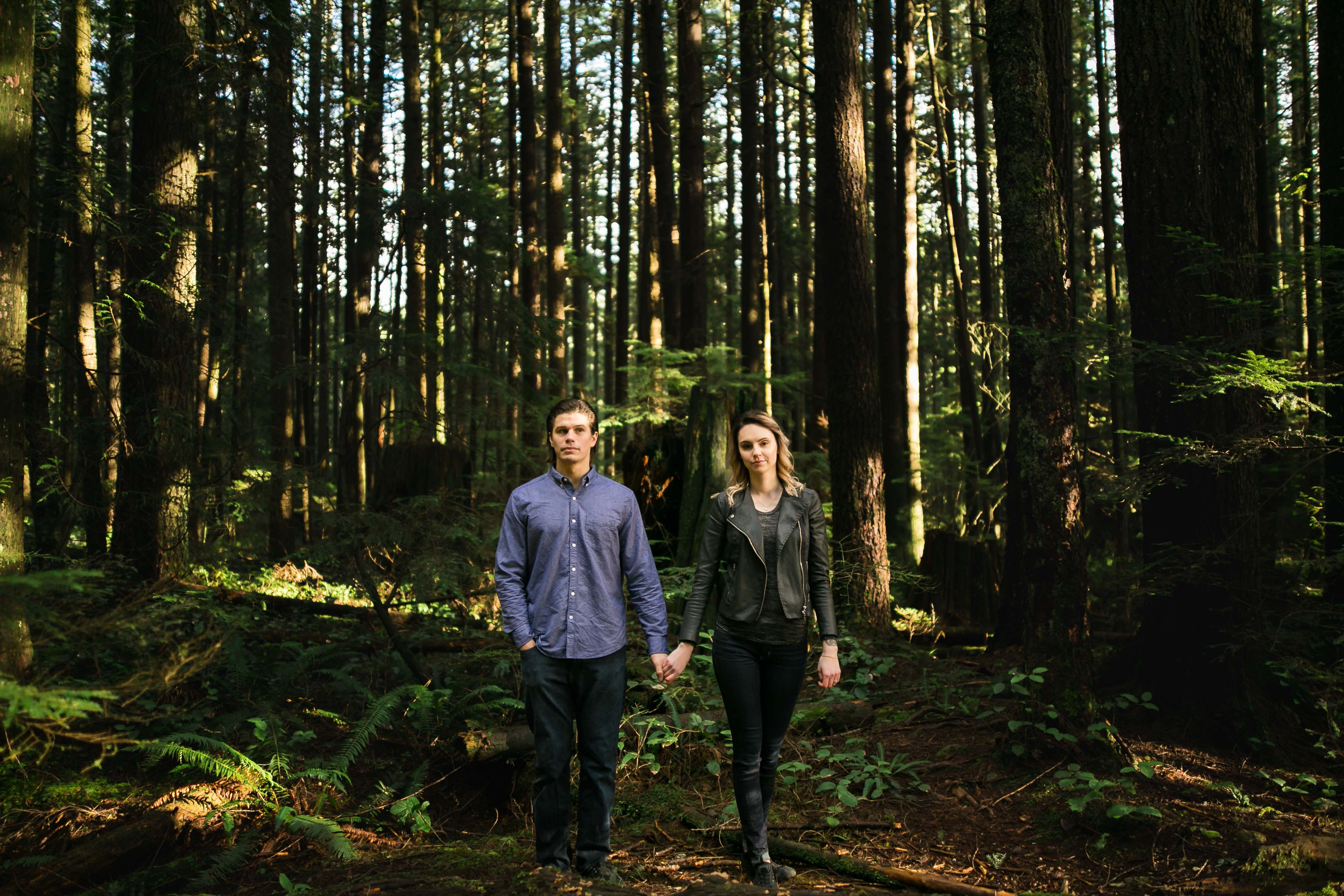 A trendy couple stand in a forest near Lynn Headwaters in North Vancouver.